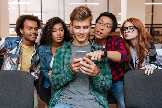 Smiling young man and his friends using mobile phone together