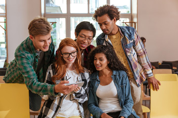Multiethnic group of young people using mobile phone together