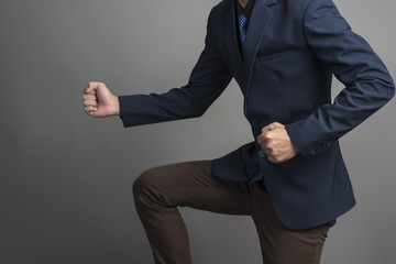 Close up of businessman in blue suit Fighting on gray background