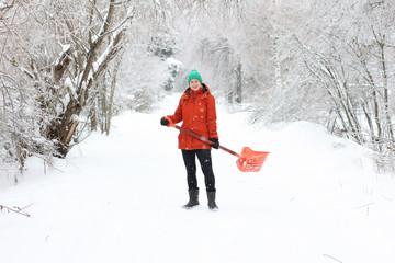 Young woman shoveling rural road