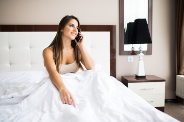 Beautiful girl speak phone in the bed