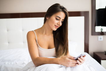 Beautiful young woman in underwear reading text message on her mobile phone and smiling.