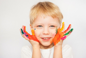 Portrait of laughing funny child with hands in paint isolated on white background. Blond baby going to make hand-prints.