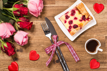 Raspberry cake on white plate, coffee, roses and red hearts on wooden background. Valentines Day background