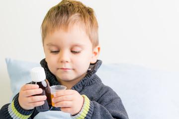 kleiner junge nimmt medikamente ein