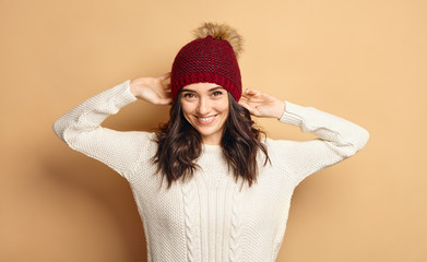 Girl in Knitted Sweater and Beanie Hat over beige background