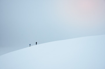 Two tourist walking in snowy landscape in norway. They travel to famous trolltunga rock