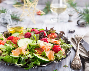 Fresh salad with smoked salmon, shrimps, raspberries and cherry tomatoes on white wooden background. Delicious Christmas themed dinner table
