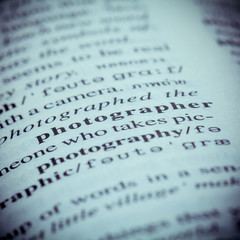 Close up of old English dictionary page with word Photographer.