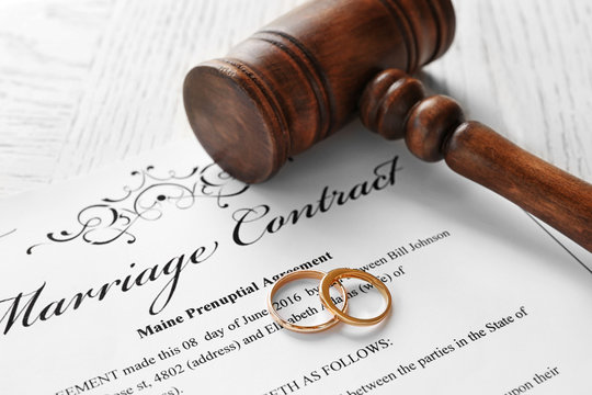 Golden wedding rings with judge gavel on marriage contract, closeup