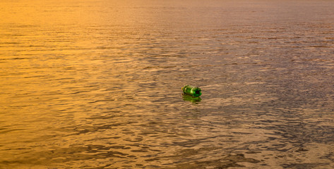 A green plastic bottle floating on the water at sunset