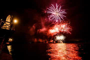 Red and violet fireworks shine over the water