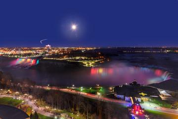 Niagara Falls lit at night by colorful lights and bright moon.