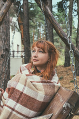 Beautiful red haired young woman with blanket on a bench at the autumn park. Coloring and processing photo