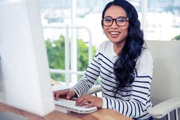 Smiling Asian woman using computer and looking at the camera