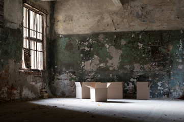 damaged, dirty room of the old abandoned building, empty boxes in the middle