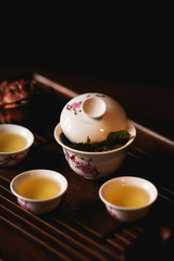 Chinese tea ceremony. Porcelain gaiwan, three cups of Chinese tea and golden frog on tea desk. Soft selective focus.