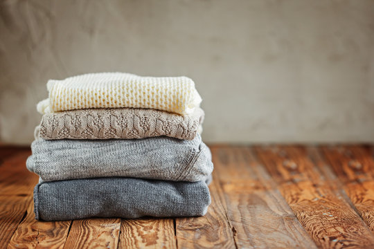 Stack of knitted winter clothes on wooden background, sweaters, space for text