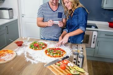 Smiling couple preparing pizza
