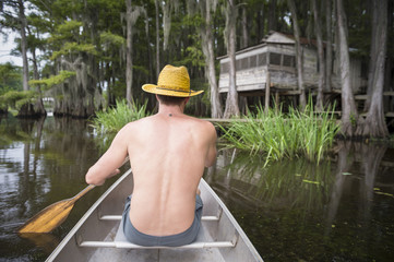 Man rowing along swamp bayou scene of the American South featuring old wooden shack built into bald cypress trees and Spanish moss in Caddo Lake Texas