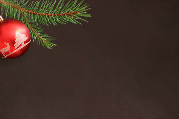 Dark background with Christmas fir branch and red ball. Top view