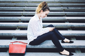 Pretty woman sitting on steps checking the phone