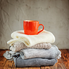 Sweaters Closeup, Stack of knitted winter clothes with red mug on wooden background.