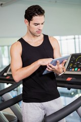 Serious man on treadmill standing with tablet