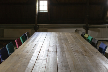 A dark wooden attic made into a meeting room with a large table and many colourful chairs.