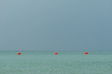 Red orange floats, buoy arrangement, make zone in bay, gulf on sea, ocean with blue gray sky in background