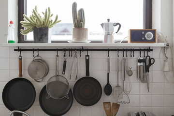 detail of a modern kitchen with pans and such hanging on a wall
