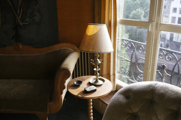 Side table with lamp besides a couch in a traditionally decorated living room.