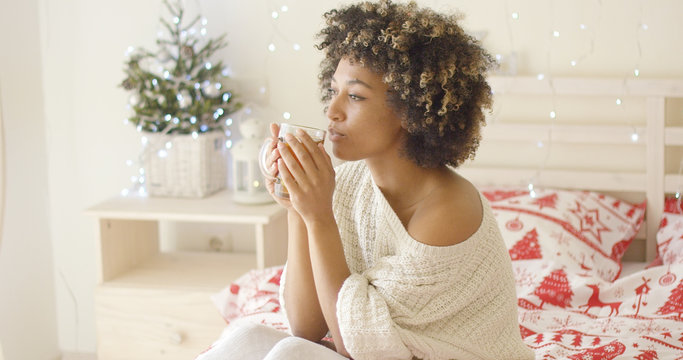 Single beautiful calm adult woman wearing white knitted sweater sipping tea from glass while seated in bed. Her bedroom has beautiful Christmas decoration.