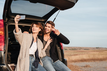 Couple taking selfie with mobile phone while sitting inside car