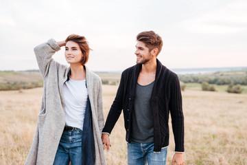 Happy young couple enjoying walk through the grass field