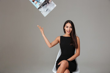 Woman in black dress sitting and throwing away magazine