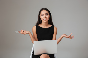 Upset frustrated woman sitting with laptop and holding mobile phone