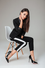 Beauty fashion model on chair looking at camera