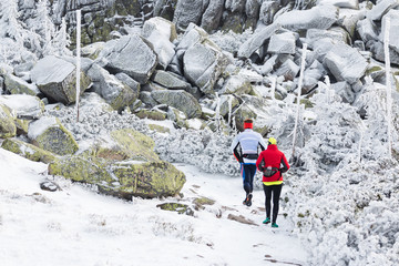 couple training trail running in freezing weather in the winter mountains with snow