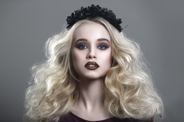 Beauty portrait of a beautiful young blonde woman with gothic make-up and decorative wreath on a gray background.