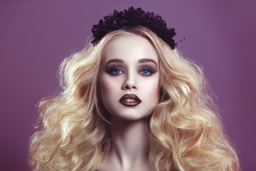Beauty portrait of a beautiful young blonde woman with gothic make-up and decorative wreath on a purple background.