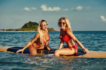 Beautiful girls having fun on a surfboard in the sea