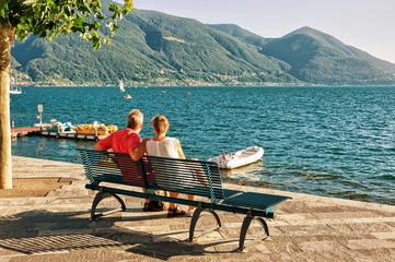 Couple sitting on bench in Ascona in Ticino Switzerland