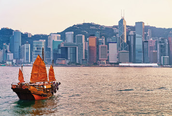 Junk boat at Victoria Harbor of Hong Kong at sunset