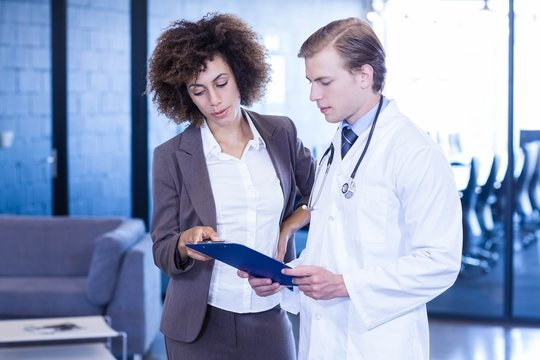 Doctor and colleague looking at medical report