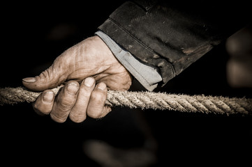 Hand pulling the rope, Grey background