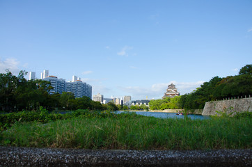 Landscape of Japanese Castle on the Island with Cityscape and Blue Sky.