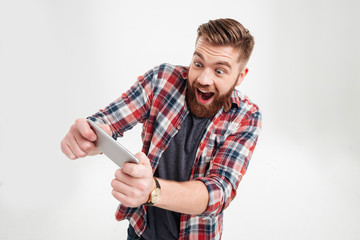Excited bearded man in plaid shirt playing on smartphone