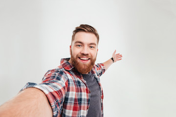 Close up portrait of a cheerful bearded man taking selfie