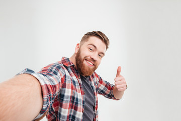 Happy casual man taking selfie and showing thumbs up gesture